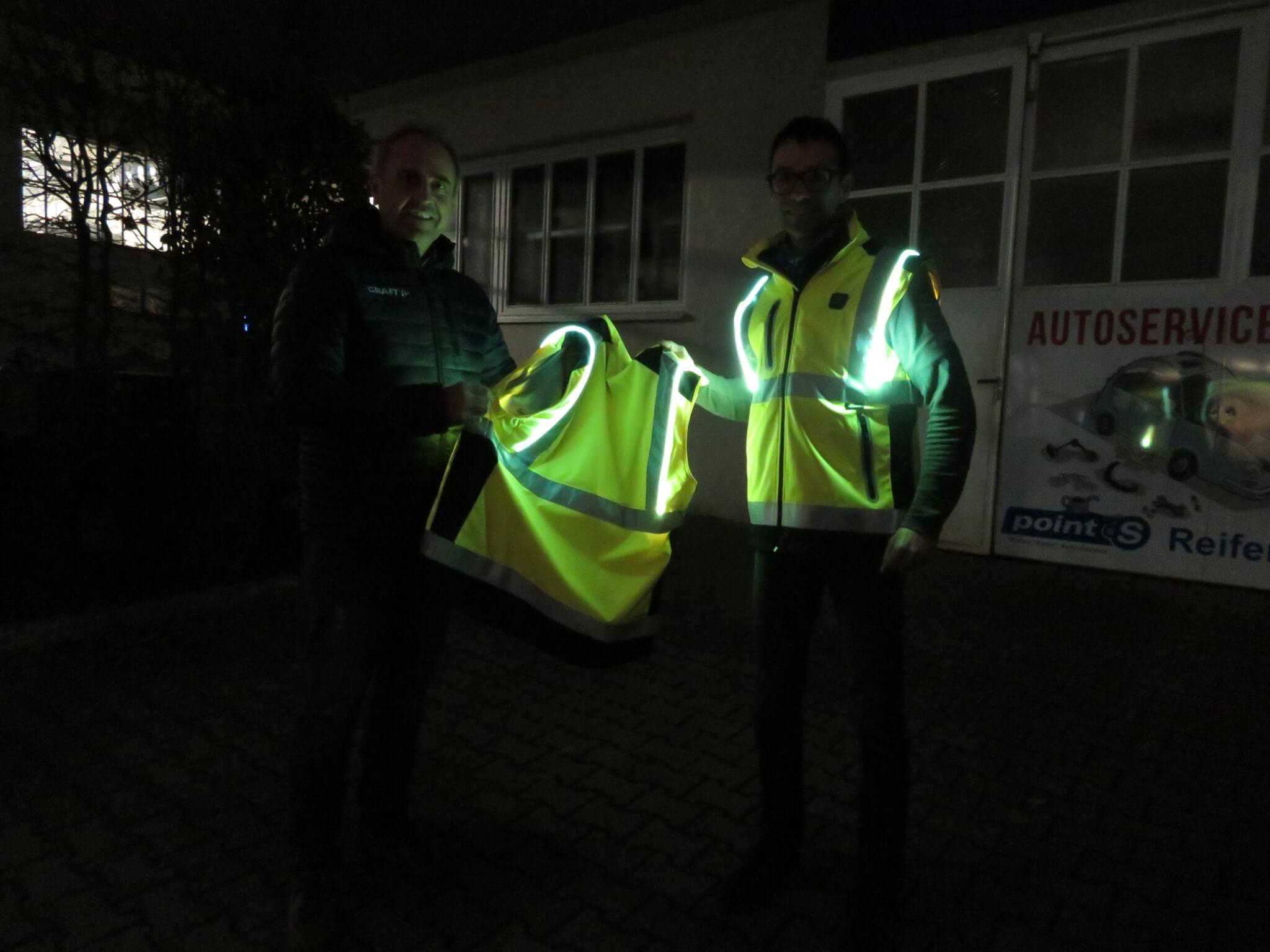 Andreas Schmaderer übergibt die innovativen Leuchtwesten an Michael Simmel.